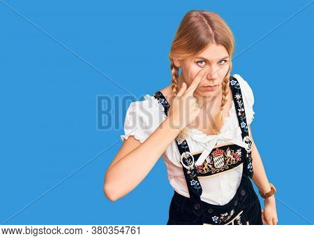 Young beautiful blonde woman wearing oktoberfest dress pointing to the eye watching you gesture, suspicious expression