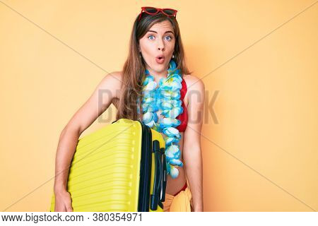 Beautiful young caucasian woman holding suitcase going on summer vacation scared and amazed with open mouth for surprise, disbelief face