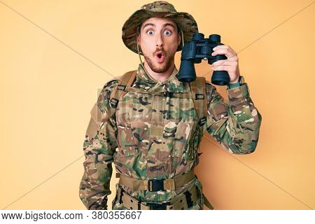 Young caucasian man wearing camouflage army uniform holding binoculars scared and amazed with open mouth for surprise, disbelief face