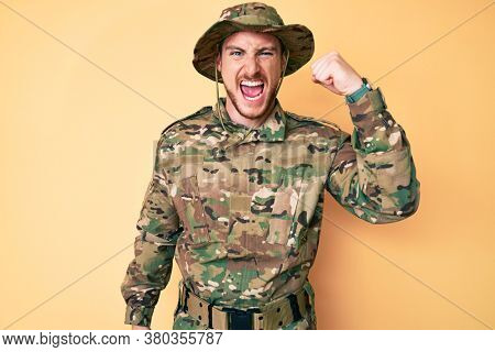 Young caucasian man wearing camouflage army uniform angry and mad raising fist frustrated and furious while shouting with anger. rage and aggressive concept.