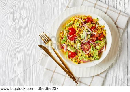Sweet Corn Salad With Avocado, Red Onion Slices And Tomatoes In A White Bowl With Golden Cutlery On