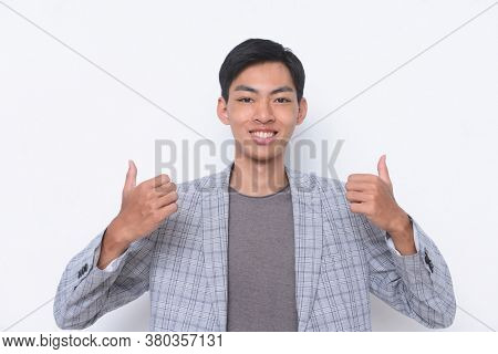young handsome  businessman    wearing in striped gray suit with gray t-shirt and blue striped tie,  success sign doing positive gesture with hand, thumbs up