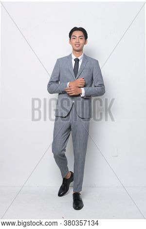 full length young handsome man wearing in gray suit ,tie with white shirt and gray pants , black shoes posing in studio