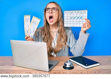 Young beautiful blonde woman holding boarding pass and travel calendar angry and mad screaming frustrated and furious, shouting with anger. rage and aggressive concept.