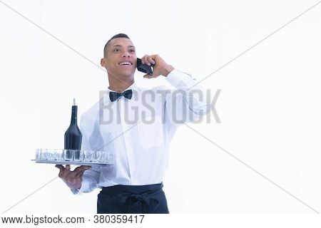 Handsome Young Waiter Talks On His Phone While Holding A Tray With Glass Shots And A Bottle On A Lig