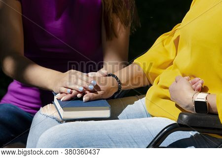 Close Up Of A Woman Using A Wheelchair Holding Hands With Another Woman On Her Lap
