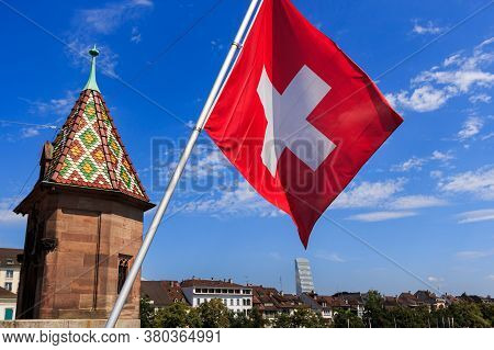 Swiss Flag On A Bridge In Basel (switzerland), Tower And City Skyline Against Bright Blue Sky