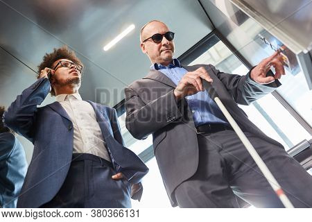 Blind man presses button in the elevator from the office