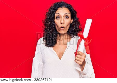 Middle age beautiful woman holding graduate degree diploma scared and amazed with open mouth for surprise, disbelief face