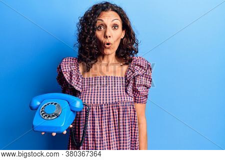 Middle age beautiful woman holding vintage telephone scared and amazed with open mouth for surprise, disbelief face