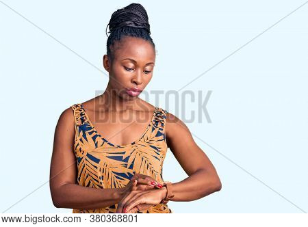 Young african american woman wearing casual clothes checking the time on wrist watch, relaxed and confident