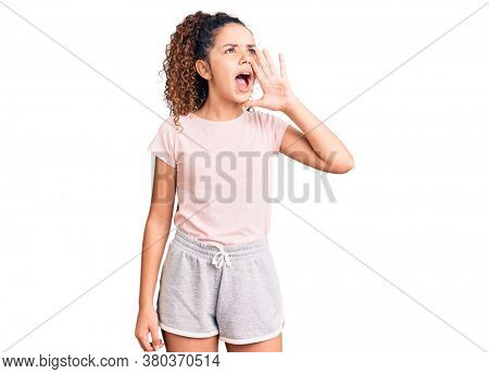 Beautiful kid girl with curly hair wearing casual clothes shouting and screaming loud to side with hand on mouth. communication concept.