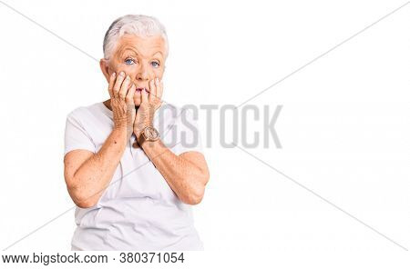 Senior beautiful woman with blue eyes and grey hair wearing casual white tshirt tired hands covering face, depression and sadness, upset and irritated for problem