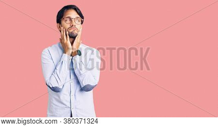 Handsome hispanic man wearing business shirt and glasses tired hands covering face, depression and sadness, upset and irritated for problem