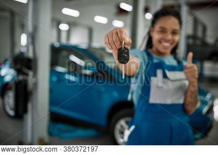 Young African American Woman, Professional Female Mechanic Smiling At Camera, Giving Car Key And Sho