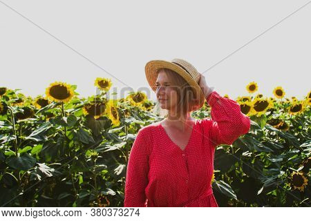 Beautiful Yound Woman In Straw Hat And Red Dress Against Sunflower Field As Natural Background. Agri