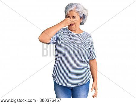 Senior woman with gray hair wearing casual striped clothes smelling something stinky and disgusting, intolerable smell, holding breath with fingers on nose. bad smell