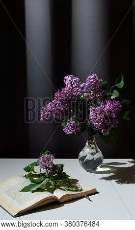 Still Life Of Bright Branch Of Lilac In The Glass Vase With Open Book On White Table On Grey Curtain