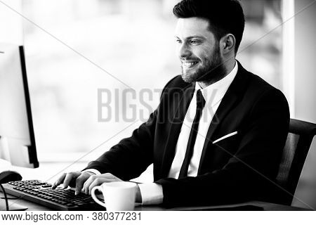 Business succsess concept. Happy smiling young businessman sitting in office and working on computer. Man in suit indoors on glass window background. Black and white, monochrome