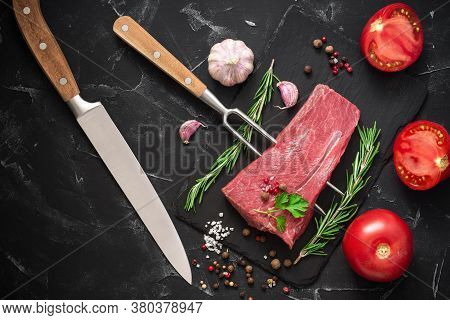 Raw Beef Tenderloin, Tomatoes, Spices, Rosemary And A Fork With A Knife On A Black Stone Background.