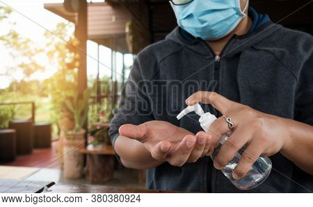 Man Wearing Medical Face Mask Using Hand Sanitizer In Coffee Shop. Man Sitting In Coffee Shop Disinf