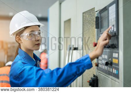 Female Factory Worker Check A Machine. Women Technician Engineering Checking Machine And Pressing Bu