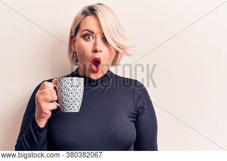 Young beautiful blonde plus size woman drinking mug of coffee over white background scared and amazed with open mouth for surprise, disbelief face