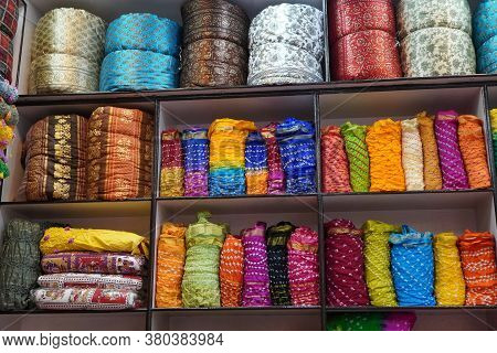 Traditional Rajasthan Dress Materials Is Neatly Stacked For Sale In A Cloth Merchant Shop In India.