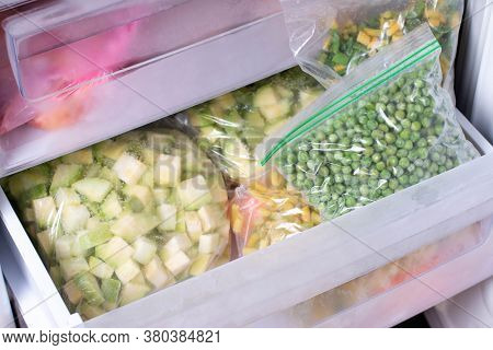 Frozen Vegetables (zucchini And Green Peas) In Plastic Bags In The Freezer. Frozen Vegetables