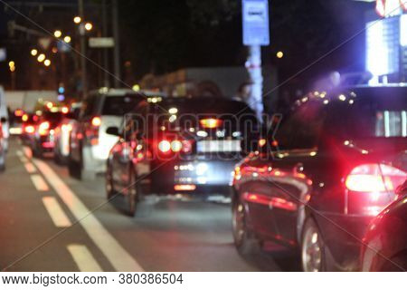 Avtomobiles With Headlights And Lights On In Night City. Cars With Headlights On. Traffic Jam In Eve