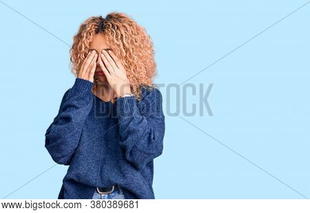 Young blonde woman with curly hair wearing casual winter sweater rubbing eyes for fatigue and headache, sleepy and tired expression. vision problem