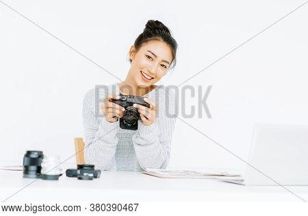Smiling Beautiful Asian Woman Photographer Holding Manual Camera And Looking At Camera While Sitting