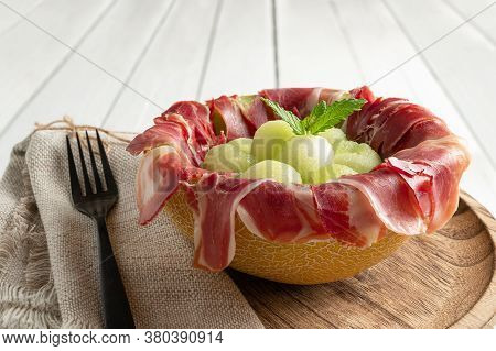 Melon With Air Dried Ham, Served In Halved Melon Stuffed With Serrano Ham And Melon Balls. Close Up