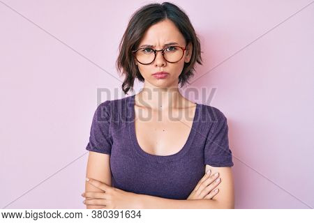 Young beautiful woman wearing casual clothes and glasses skeptic and nervous, disapproving expression on face with crossed arms. negative person.