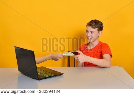 A Man's Hand From A Laptop Monitor Holds Out Dollars To The User. Online Earnings Concept