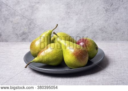 Green Pears With Red Sides In Grey Plate On Grey Background