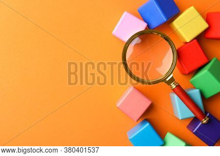 Different Colorful Cubes And Magnifier Glass On Orange Background, Flat Lay With Space For Text. Fin