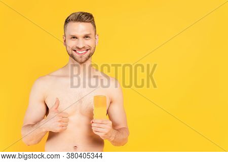 Muscular Man Showing Thumb Up And Holding Bottle With Sunblock Isolated On Yellow