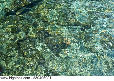 Abstract Texture Of Clear Turquoise Sea Water With A Rocky Bottom