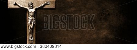 Body Of Christ On Wooden Cross On Long Narrow Background In Dark Brown Tones Suitable For Header - G