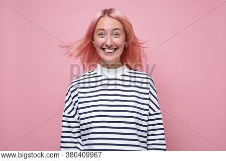 Happy Young Woman With Pink Dyed Has Tender Smile, Looks With Charming Expression
