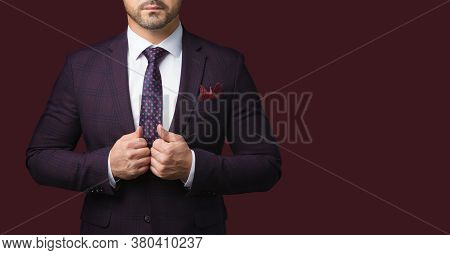 Sharp Dressed Man In Jacket And Tie Isolated On Dark Red Background. Picture For Advertising A Men's