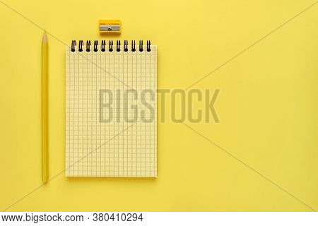 Yellow Spring Notepad And Yellow Pencil Are On The Left Side Of The Screen On Yellow Background. Squ