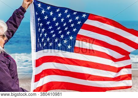 Caucasian Blonde Woman Waving An American Flag And Looking At Sea. Usa Flag For Independence Day