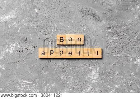 Bon Appetit Word Written On Wood Block. Bon Appetit Text On Cement Table For Your Desing, Concept