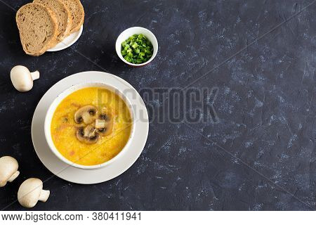 Champignon Soup In A White Bowl. Whole Champignons, Bread And Cut Green Onions On A Blue Background.