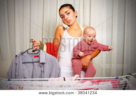 Tired Mother With Crying Baby At Home