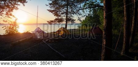 Panorama of the campground with two hiking tents set on the area and one sailing catamaran beached on the coast.