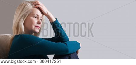 Woman Suffering From Stress Or A Headache Grimacing In Pain. Sad Depressed Woman At Home Sitting On