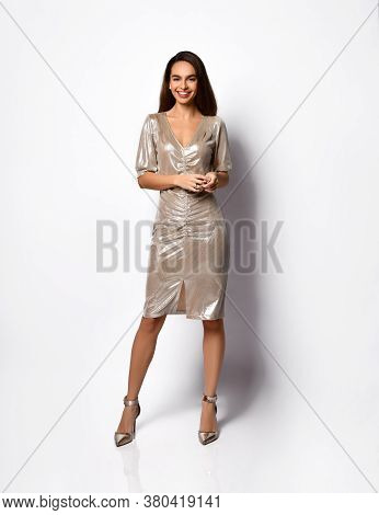 Elegant Young Woman With Slim Long Legs Calmly Posing In A Short Silver Dress With Sequins And High